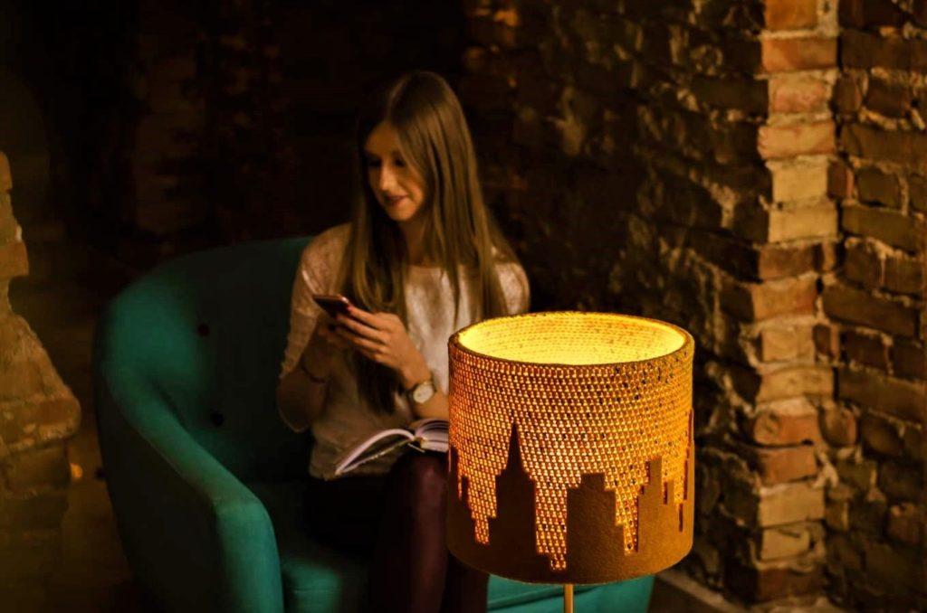 dziewczyna siedząca na fotelu dzwoni do przyjaciółki, a na stoliku stoi designerska lampa z motywem miasta