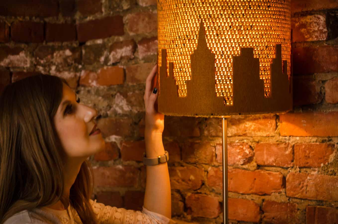 Kobieta delikatnie dotyka abażur od lampy
