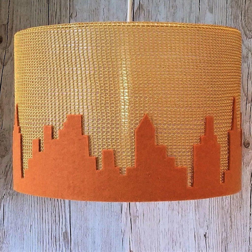złoty abażur zrobiony ręcznie na szydełku z motywem miasta
