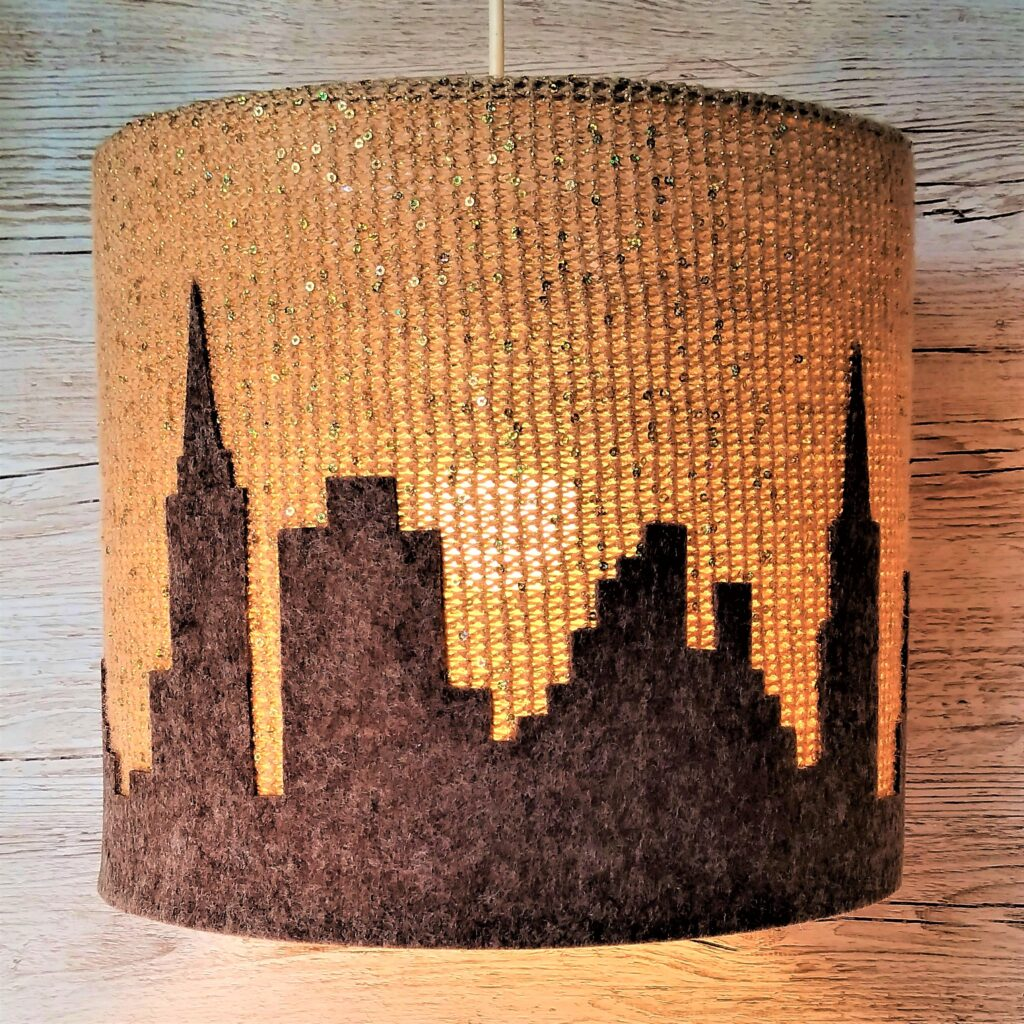 złoto-brązowa lampa sufitowa z motywem miasta