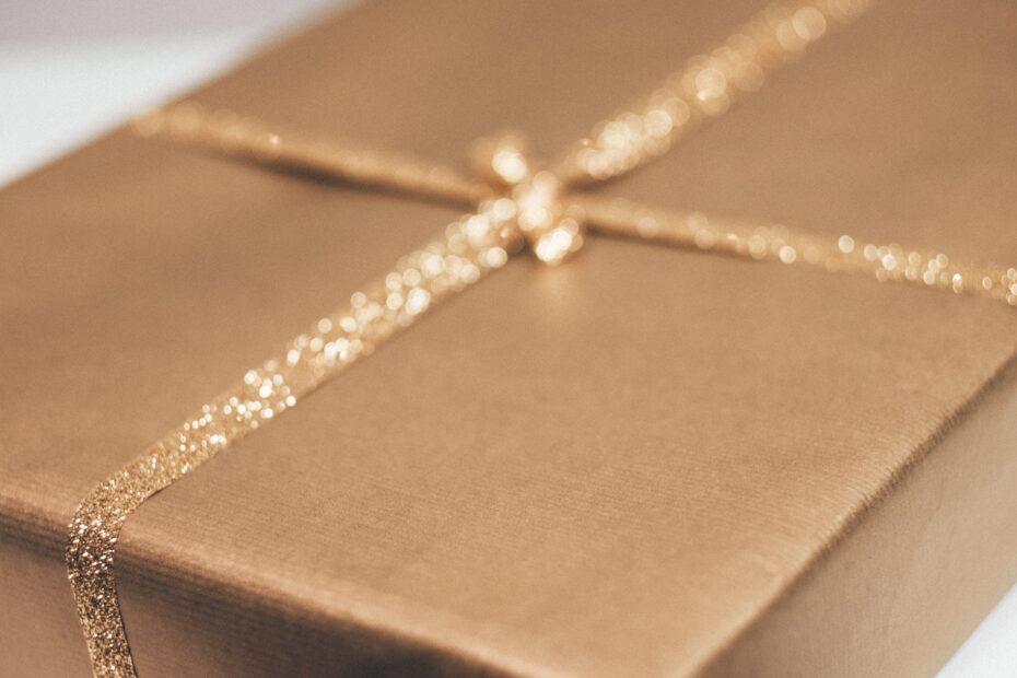 prezent niespodzianka zapakowany w szary papier i złota wstążka