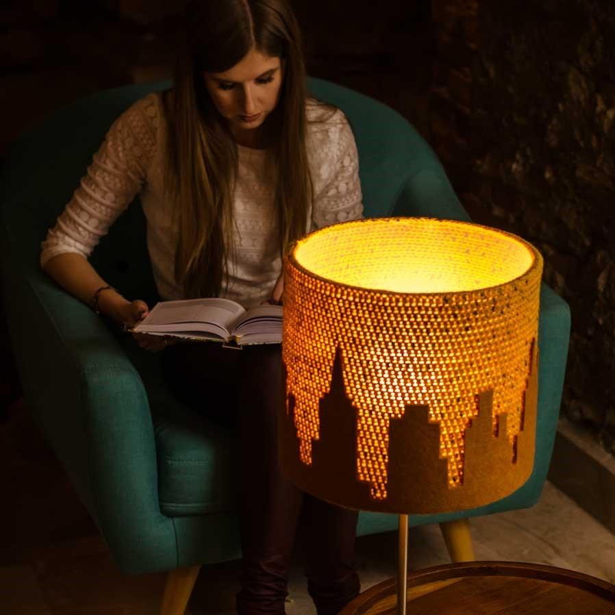 kobieta siedzi na fotelu i czyta książkę przy zapalonej pięknej lampie wykonanej na szydełku